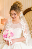 美丽的新娘纵向年轻人 女孩在旅馆客房摆在 夫人坐与玫瑰花束由 库存照片