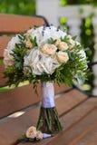 美丽的新娘花束和钮扣眼上插的花在一个长木凳 库存图片