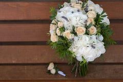 美丽的新娘花束和钮扣眼上插的花在一个长木凳 免版税库存照片