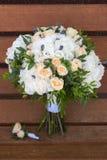 美丽的新娘花束和钮扣眼上插的花在一个长木凳 库存照片