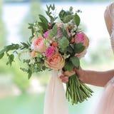 美丽的新娘花束在新娘的手上 桃子玫瑰婚姻的花束由大卫奥斯汀,单一领袖桃红色的上升了水色, 免版税库存照片