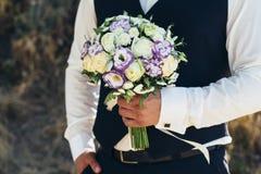 美丽的新娘花束在新郎的手上 白玫瑰婚礼花束,金丝桃属植物, lisianthus,菊花,南北美洲香草 免版税库存图片