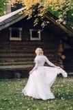 美丽的新娘转动她自己在木房子背景的振翼的礼服的 回到视图 附庸风雅 免版税图库摄影
