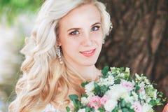 美丽的新娘 婚礼发型和组成 拿着花束的婚礼礼服的年轻新娘 免版税库存图片
