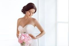 美丽的新娘 婚礼发型构成花豪华时尚礼服和花束  库存照片