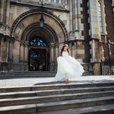美丽的新娘离开教会并且去在楼上 库存照片