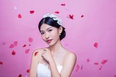 美丽的新娘画象有玫瑰花瓣的在反对桃红色背景的空中 免版税图库摄影