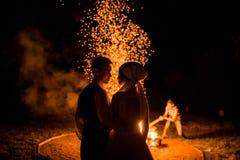 美丽的新婚佳偶的浪漫画象在灼烧的火的火焰的背景的晚上 免版税库存照片