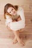 美丽的无忧无虑的年轻偶然妇女坐地板。 免版税库存图片