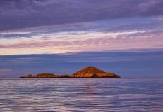 美丽的日落天空和反射在风平浪静 免版税库存图片