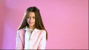美丽的时兴的女孩在桃红色背景摆在 股票视频