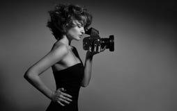 美丽的时尚妇女,模型黑白照片观看在照片照相机 免版税库存图片