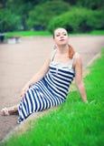 年轻美丽的时髦的女人坐草坪 免版税库存图片