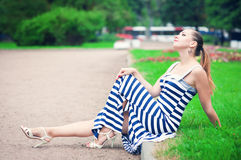 年轻美丽的时髦的女人坐草坪 免版税库存照片