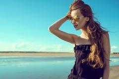 年轻美丽的时髦的妇女佩带的黑色开放肩膀连裤外衣和时髦回合反映了站立在水池的太阳镜 免版税库存图片