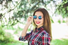 美丽的时髦的妇女在公园微笑并且放松 拷贝空间 图库摄影