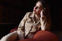 美丽的时髦的小姐画象衣服的坐红色沙发 库存照片