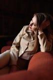 美丽的时髦的小姐画象衣服的坐红色沙发 免版税库存照片