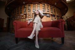 美丽的时髦的小姐画象衣服的坐红色沙发 库存图片