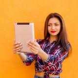 美丽的时髦的微笑的妇女由片剂做selfie 橙色背景 拷贝空间 库存图片