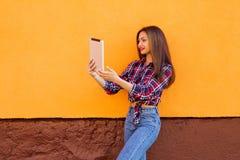 美丽的时髦的微笑的妇女由片剂做selfie 橙色背景 拷贝空间 免版税库存图片