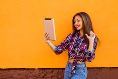美丽的时髦的微笑的妇女由片剂做selfie 橙色背景 拷贝空间 免版税图库摄影