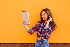 美丽的时髦的微笑的妇女由片剂做selfie 橙色背景 拷贝空间 库存照片
