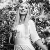美丽的时髦的礼服的年轻人微笑的白肤金发的妇女黑白的室外画象  免版税库存照片