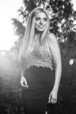 美丽的时髦的礼服的年轻人微笑的白肤金发的妇女黑白的室外画象  免版税图库摄影