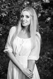 美丽的时髦的礼服的年轻人微笑的白肤金发的妇女黑白的室外画象  库存照片