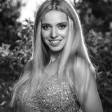 美丽的时髦的礼服的年轻人微笑的白肤金发的妇女黑白的室外画象  图库摄影