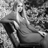 美丽的时髦的长的礼服的年轻人微笑的白肤金发的妇女黑白的室外画象  免版税库存照片