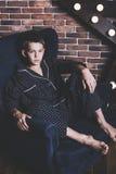 美丽的时髦青少年的男孩在家坐椅子 免版税库存图片