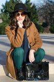 美丽的时兴的女孩在公园坐晴朗的秋天天 免版税图库摄影