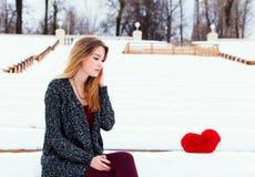 美丽的时兴的女孩在冬天坐长凳 免版税库存照片