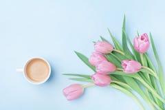 美丽的春天早餐在母亲或妇女天 桃红色郁金香和咖啡杯花束在蓝色淡色台式视图 平的位置 图库摄影