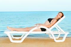 美丽的晒日光浴的妇女 免版税库存照片