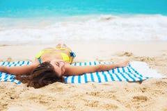 年轻美丽的晒黑妇女说谎的热带海滩 库存图片