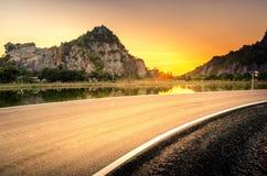 美丽的曲线路美好的日落山背景 库存图片