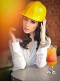 美丽的有在橙汁前面的黄色盔甲的妇女土木工程师休假 有白色衬衣的年轻女性建筑师 免版税图库摄影