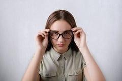 美丽的有女孩佩带的衬衣画象长的头发被隔绝在戴大眼镜的灰色背景接触她的玻璃 免版税库存图片