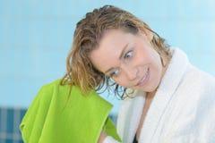 美丽的有毛巾的妇女干毛发在游泳以后 库存照片