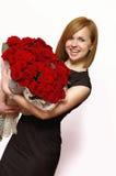 美丽的有玫瑰的年轻人微笑的金发碧眼的女人 免版税图库摄影