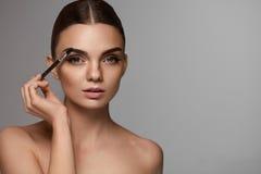 美丽的有眉头工具的妇女掠过的眼眉 免版税库存照片