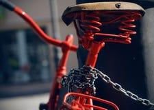 美丽的有老马鞍的葡萄酒红色自行车 免版税库存图片