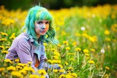 美丽的有绿色头发的行家供选择的少妇在草坐用蒲公英在公园 免版税库存照片