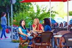 美丽的朋友坐咖啡馆大阳台 库存图片