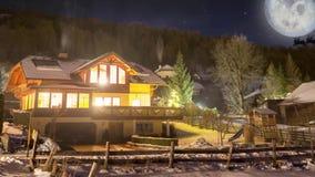 美丽的木房子英尺长度雪盖的高山的在晚上 圣诞老人骑马剪影在雪橇的 股票录像