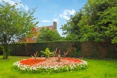 美丽的杂色的花圃在格林威治公园,有一个村庄屋顶的伦敦在树后在背景中在一个夏日 库存图片