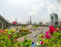 美丽的桃红色九重葛花有胜利纪念碑看法在一个圆形交通路口的中心在交叉点的 库存照片